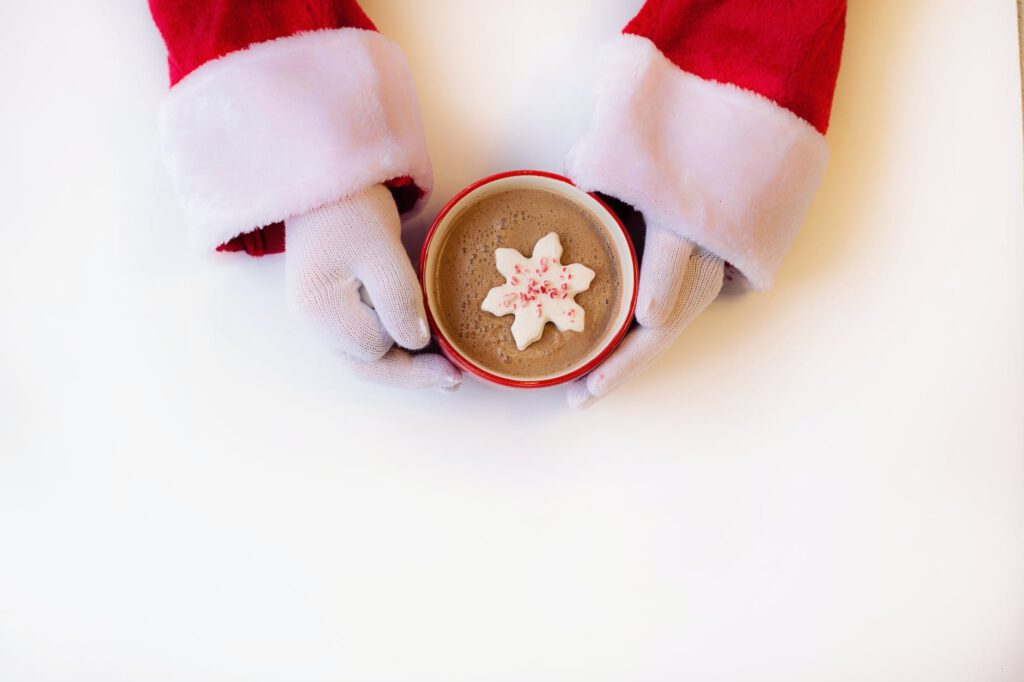 person wearing white gloves holding cup of hot cocoa