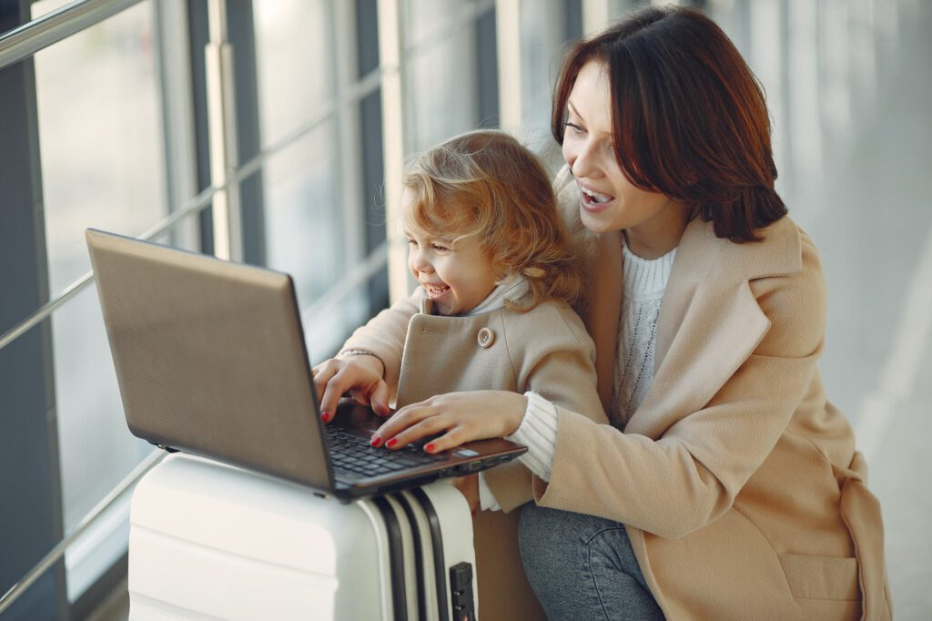 delighted mother with daughter typing on laptop in airport
