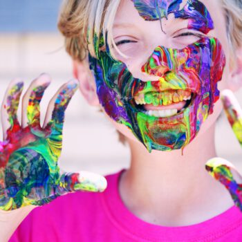 boy in pink crew neck top with paints on his hands and face