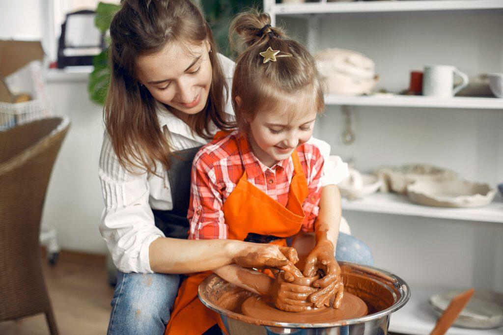 female potter teaching daughter molding on pottery wheel