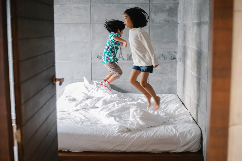 funny barefooted little ethnic siblings jumping on bed
