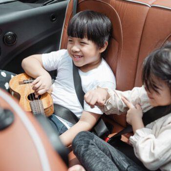 happy asian kids traveling in car