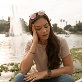 woman in brown t shirt and blue denim jeans sitting on gray rock near body of with with with with